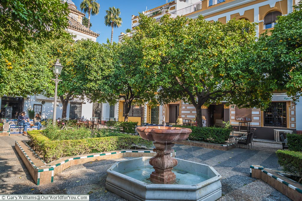 A small red marble fountain in the centre of one of the many small squares you find yourself getting lost in in Seville