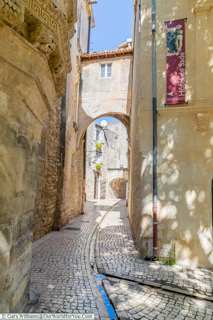 Looking a long and narrow cobbled passageway, under an archway, in centre of Saint Remy de Provence.  A channel runs down the centre of the lane to allow rainwater to flow away.