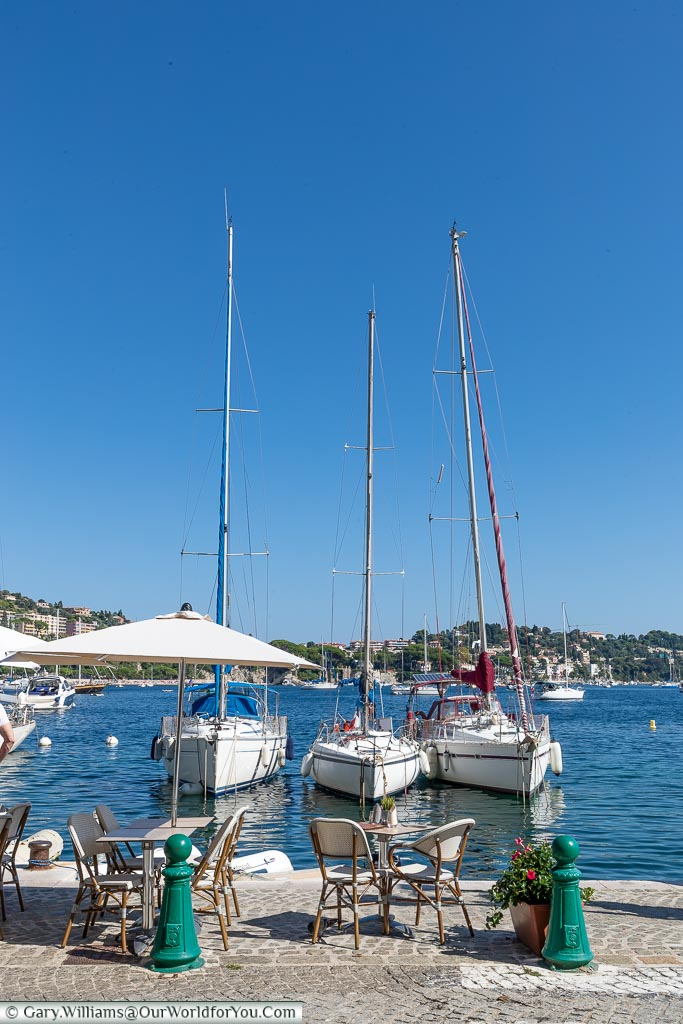 A table & chairs at the edge of the harbour of Villefranche-sur-Mer in front of 3 small yachts.