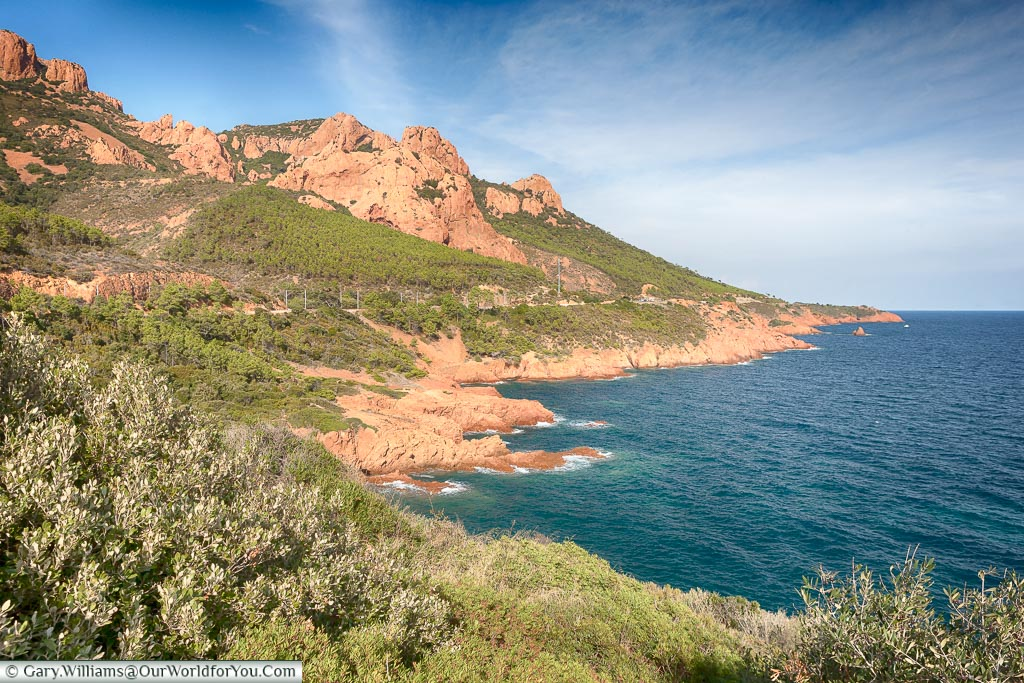 A view of the rugged red rocks and the deep blue waters of the Cote d'Azur.  Hugging the coastline is the road known as the Corniche d'Or.