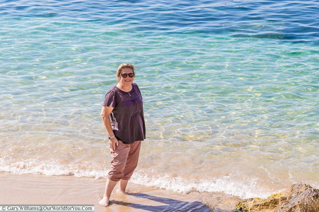 Janis with her toes in the Mediterranean sea as it laps up to the beach in Villefranche-sur-Mer.