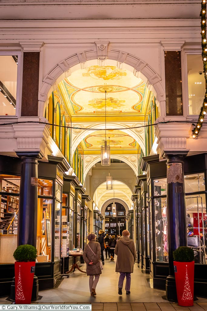 A passage off Neuer Wall in Hamburg with an ornately decorated ceiling and rows of sophisticated shops lining either side.