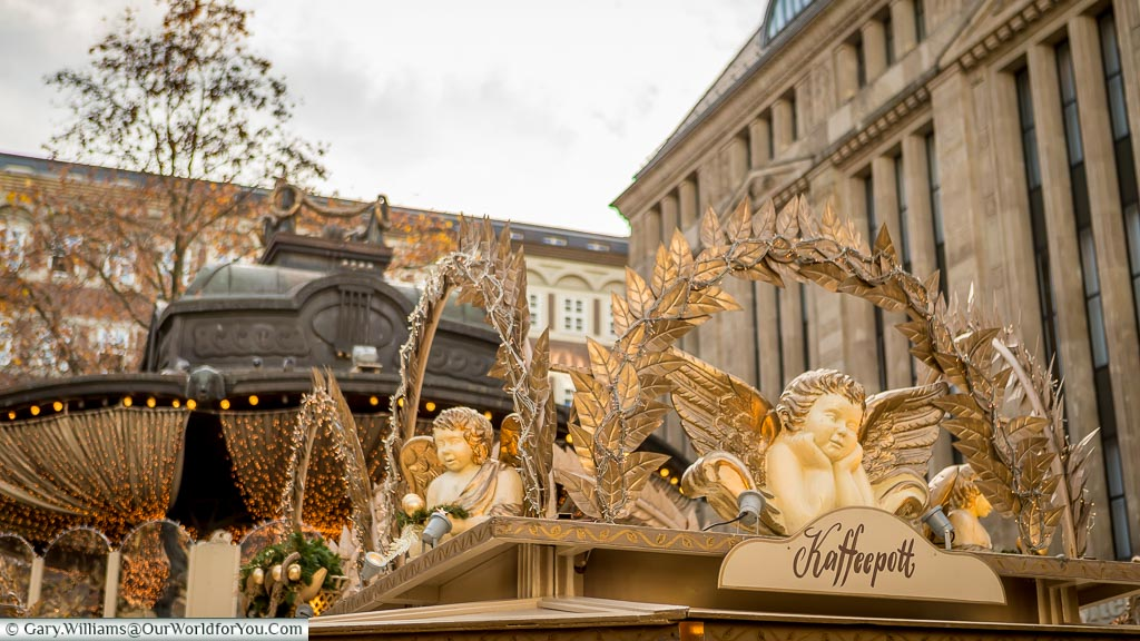 Angel decorations, trimmed in gold, on the huts of the Angel market in Düsseldorf with the aged bronze roof of the bandstand in the centre of Heinrich-Heine-Platz in the background.