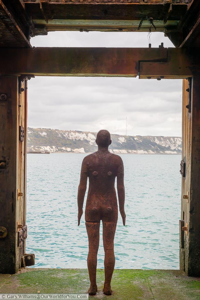 "Looking from behind the Antony Gormley installation ""Another Time XVIII"" in the harbour arm onto the water and the white cliffs."