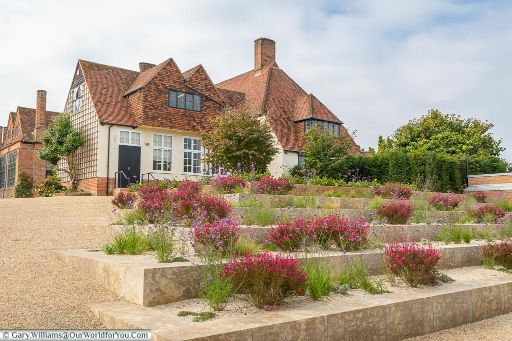 Raised flower beds with cerise coloured flowers leading to  a pretty house at the entrance to RHS Gardens Wisley