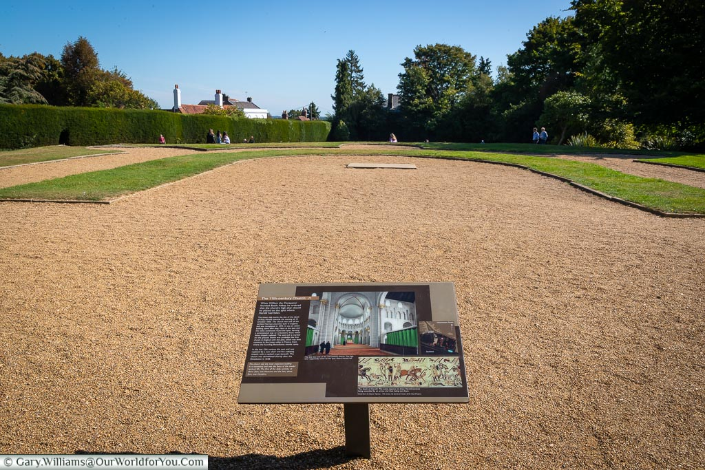 An open-air view of the area where the Battle Abbey high altar once stood.  The boundaries are marked out with grass, and an information board gives more details of the original layout.