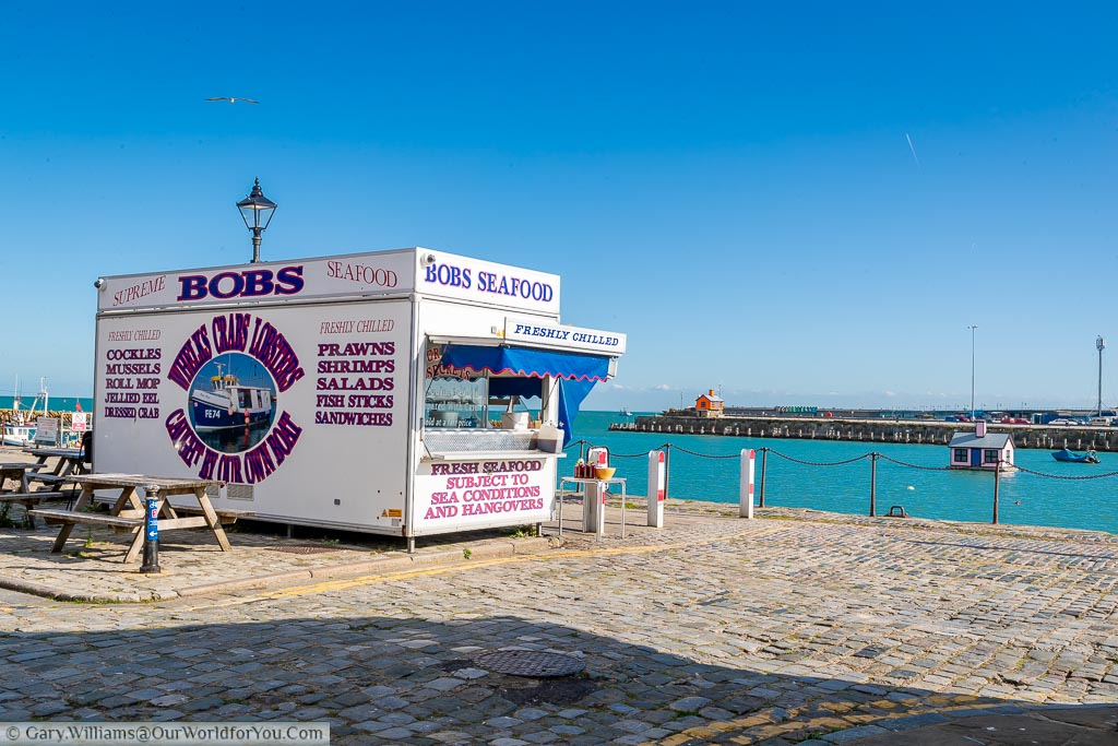 Bob's Seafood stall overlooking the harbour under a deep blue sky.
