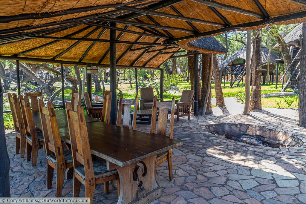 The dining table in the boma next to the open-air fire pit where the campfire is lit every evening.