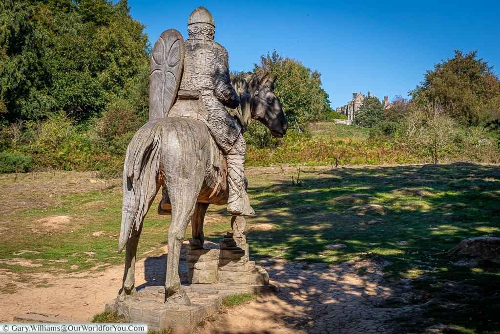 A wooden statue of a Norman soldier on horseback looking across the battlefield towards the Abbot's house.