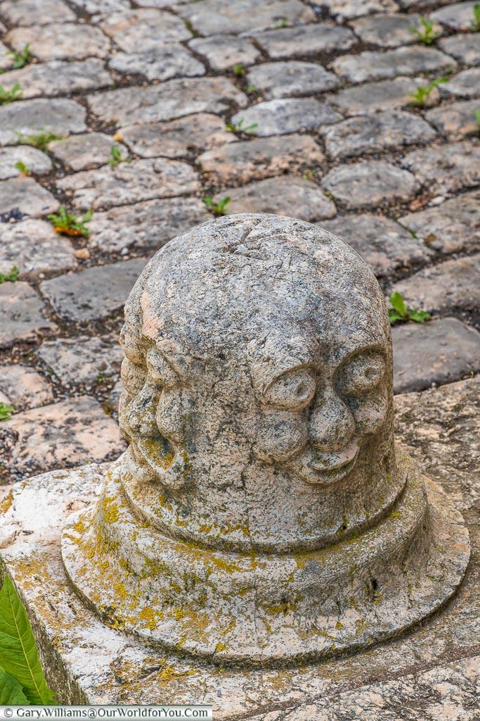 A face carved on a stone bollard.