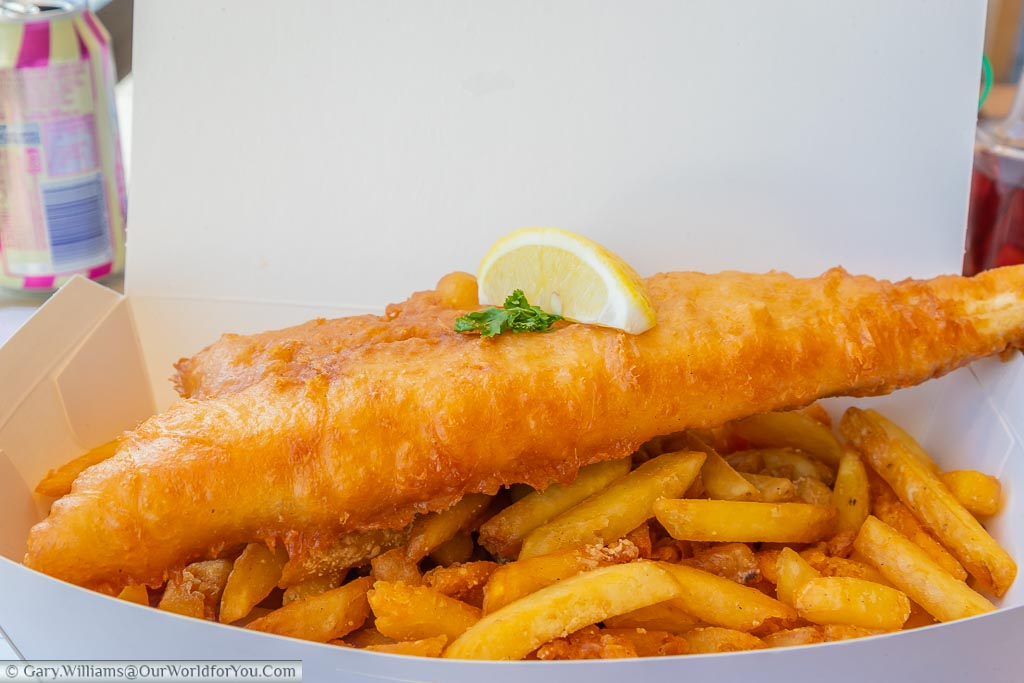 A portion of cod in crispy batter sitting on a bed of crispy garlic fries from the Smokehouse served in white cardboard packaging.