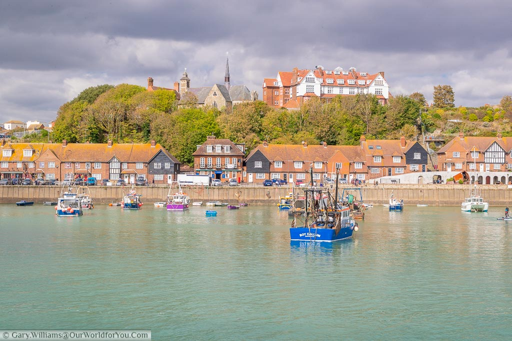 A collection of small fishing boats in Folkestone harbour in front of The Strade, a parade of pubs & homes along the harbour edge.  Behind that, on the hill, is St Peter's Church.