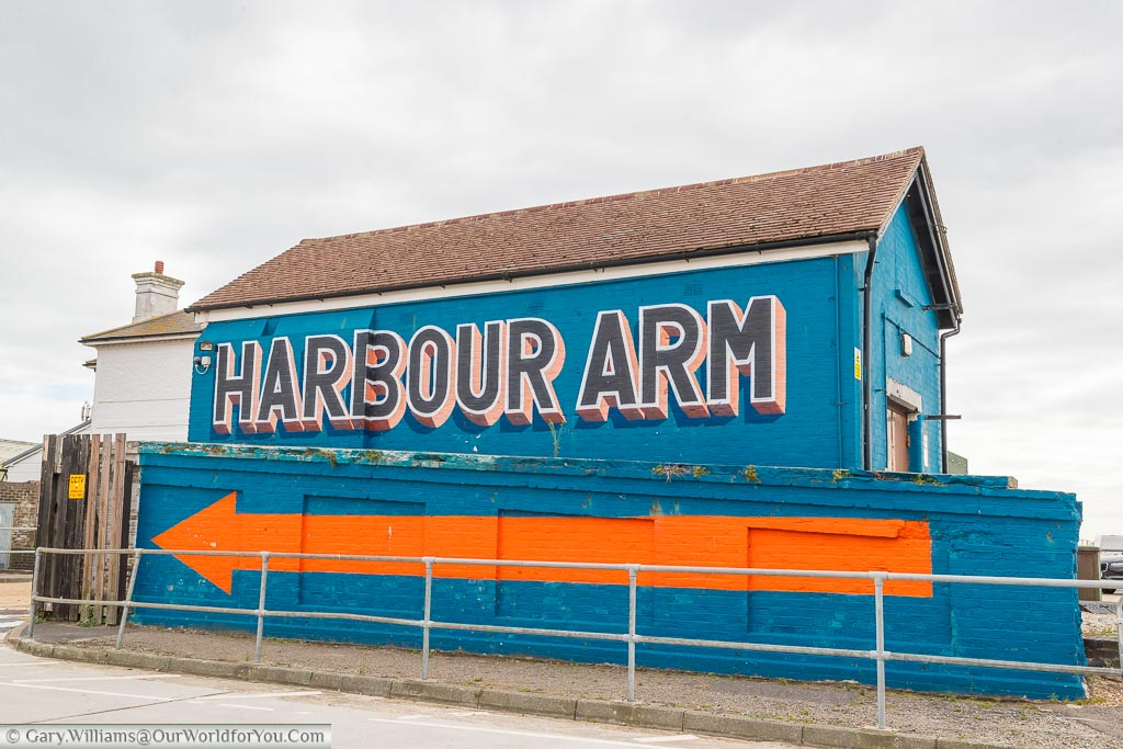 A blue brick building with a bright orange arrow and labelled Harbour Arm,