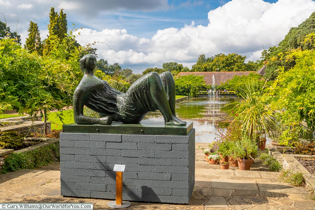 Henry Moore's statue 'Draped Reclining Figure' in front of the Jellicoe canal and the water lily pavilion.