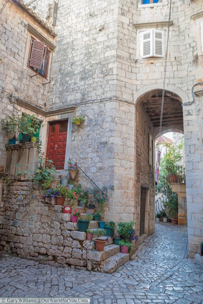 A small courtyard with cobbled paths, stop steps leading to the buildings made from golden-coloured stone.  Flowerpots decorate the steps and provide the colour in the scene.