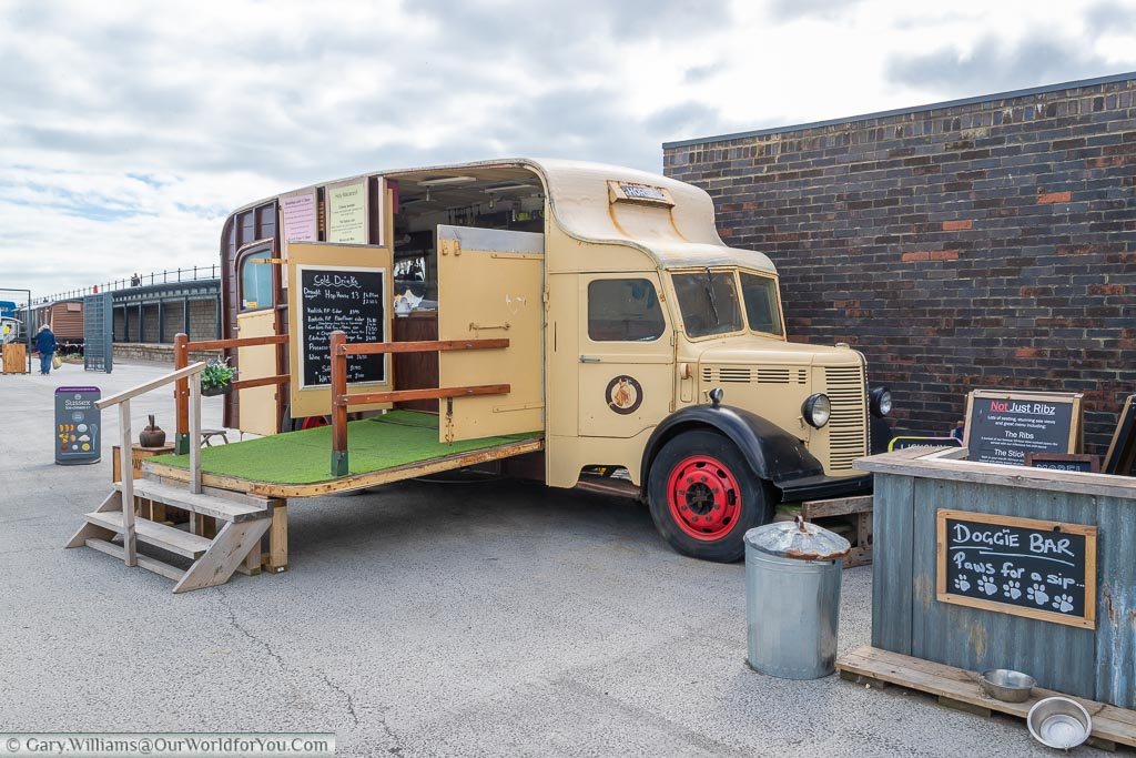A cream coloured 1930's Bedford horsebox truck converted to a takeout bar & restaurant.