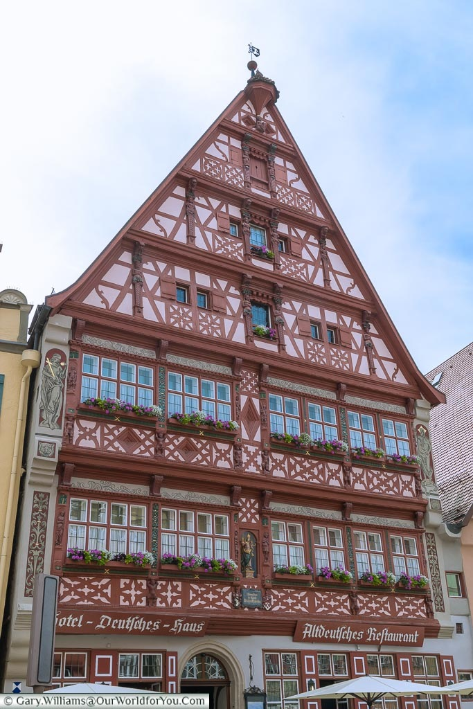 The ornate pink & red, half-timbered facade of the Hotel Deutsches Haus.  One of the many beautiful traditional buildings that make up Dinkelsbühl.