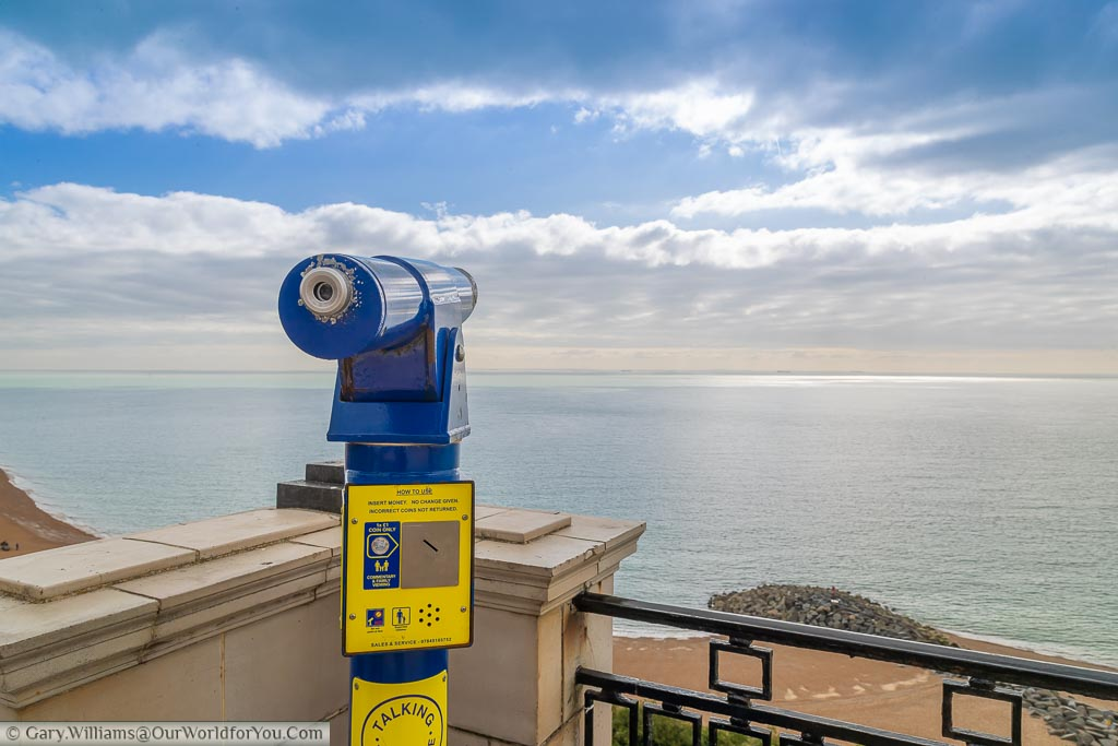 A blue fixed telescope overlooking the English change towards France as blue skies start to appear on an otherwise cloudy day.