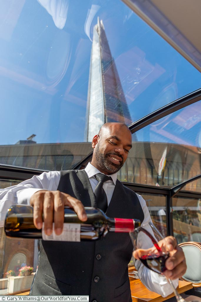 Jerome, our waiter, pouring us a glass of red wine with The Shard in the background visible through the panoramic roof.