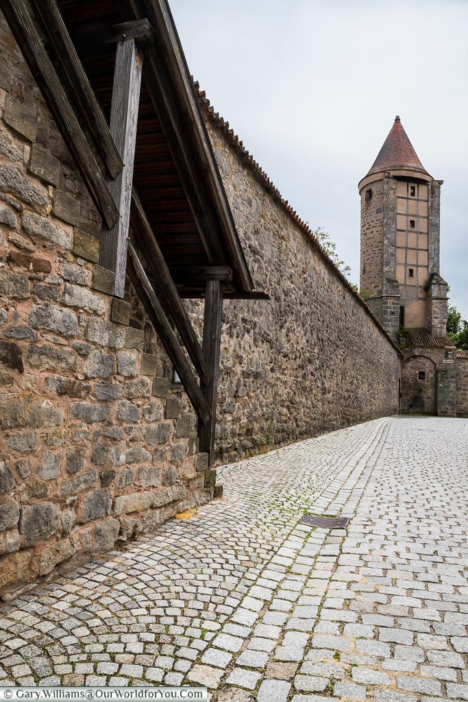 A view along a cobbled lane inside the city walls with the Krugsturm tower at the far end.