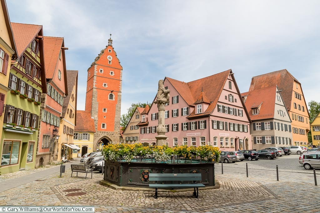 Looking over the Löwenbrunnen fountain with the Wörnitz gate at the base of a tower.  All the buildings again are painted in traditional colours.