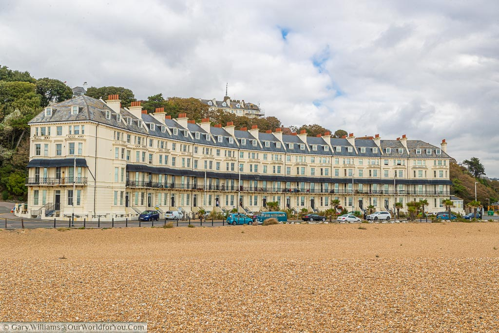 Marine Crescent, and Edwardian apartment block four-storeys high, painted in a cream colour with a grey slate roof, in front of the shingle beach.