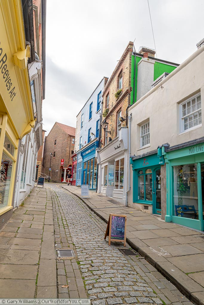 The top of the narrow cobbled Old High Street with more brightly coloured unique shops.