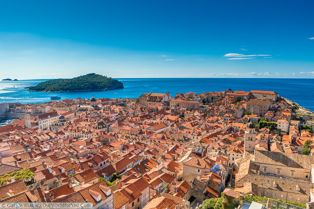 The old city of Dubrovnik from the city walls, across the orange tiled roofs leading to the deep blue waters of the Adriatic.
