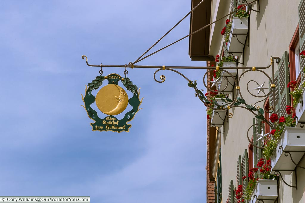 A beautiful, traditional, smiling man-on-the-moon wrought iron Inn sign.