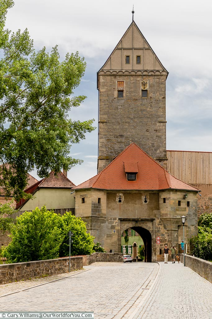 A cobbled lane leads into one of the cities gatehouses topped with the Rothenburger Tor.