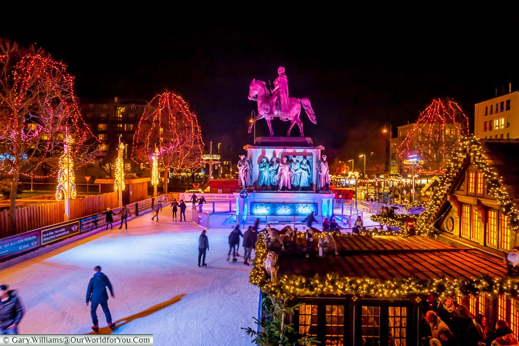 The Cologne ice rink from the bridge that straddles it, looking to the loop around the statue to Friedrich Wilhelm III on horseback.  In the foreground to the right is a beautifully crafted and ornate cabin serving gluhwein.