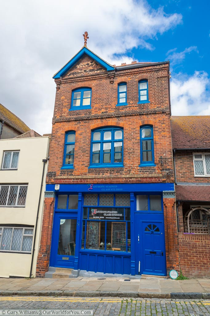 A red brick three-storey building with a deep blue frontage, and blue window frames, that now houses a stained glass window shop.