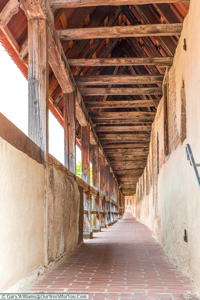Looking down the path that runs along the old city walls, covered by a red-tiled roof over a timber framework.