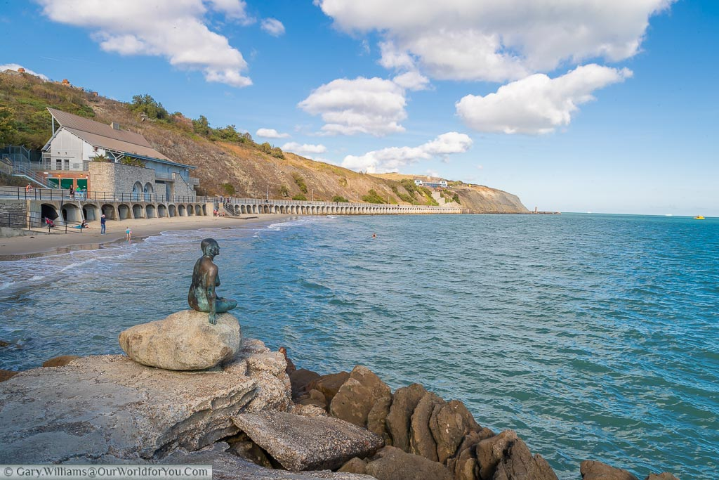 The Folkestone Mermaid by Cornelia Parker, perched on a rock overlooking the sea.