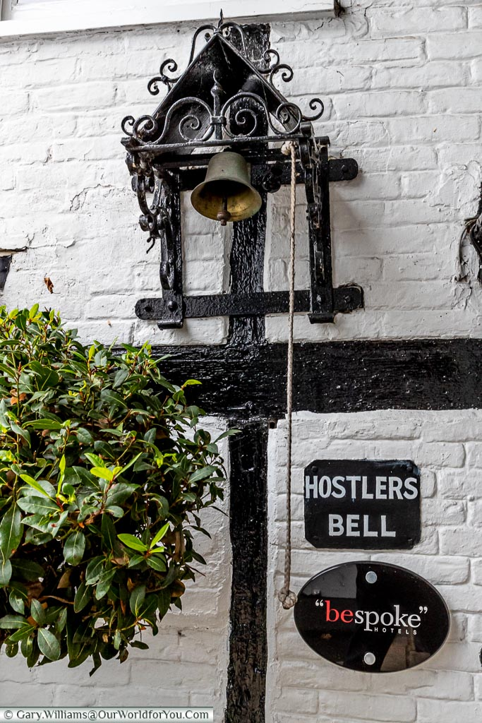 "A bell mechanism, with a rope handing down, labelled as the 'Hostlers Bell' above a sign for ""bespoke hotels""."