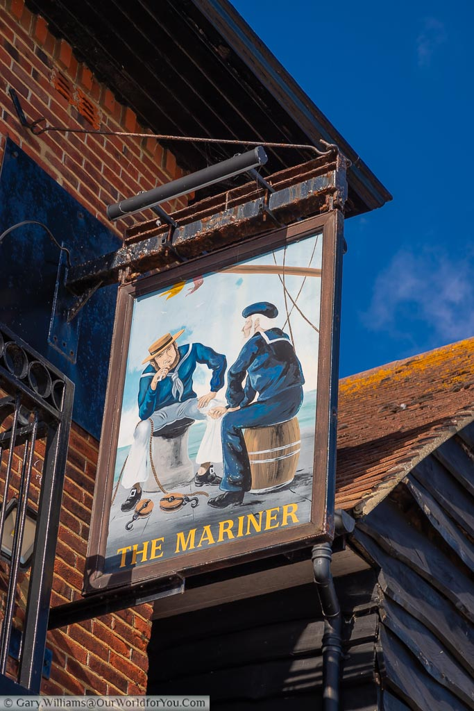 The Mariner pub sign depicting two sailors seated by the edge of the harbour in conversation.
