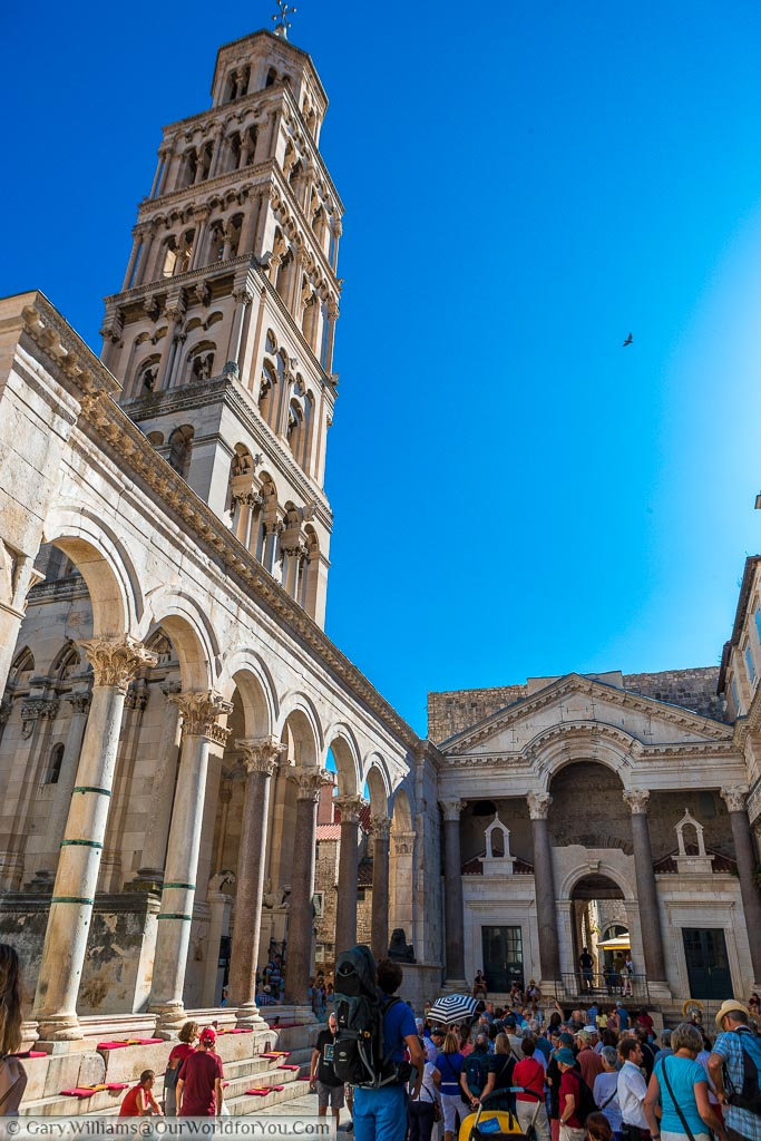 Inside the Diocletian Palace in Split looking up at the Roman Peristyle against bright blue skies.