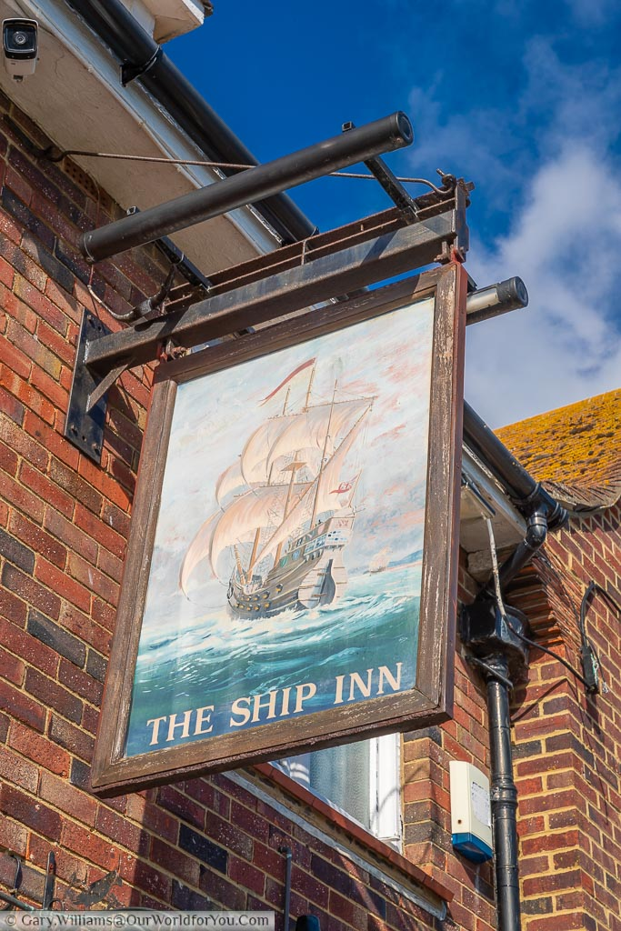 The Ship Inn pub sign with a painted 17th-century warship on the ocean wave.