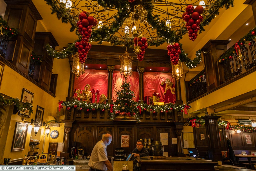 Inside the Christmas decorated Bierhaus en d'r Salzgass, a traditional Kolsch pub with beer barrel on the bar.
