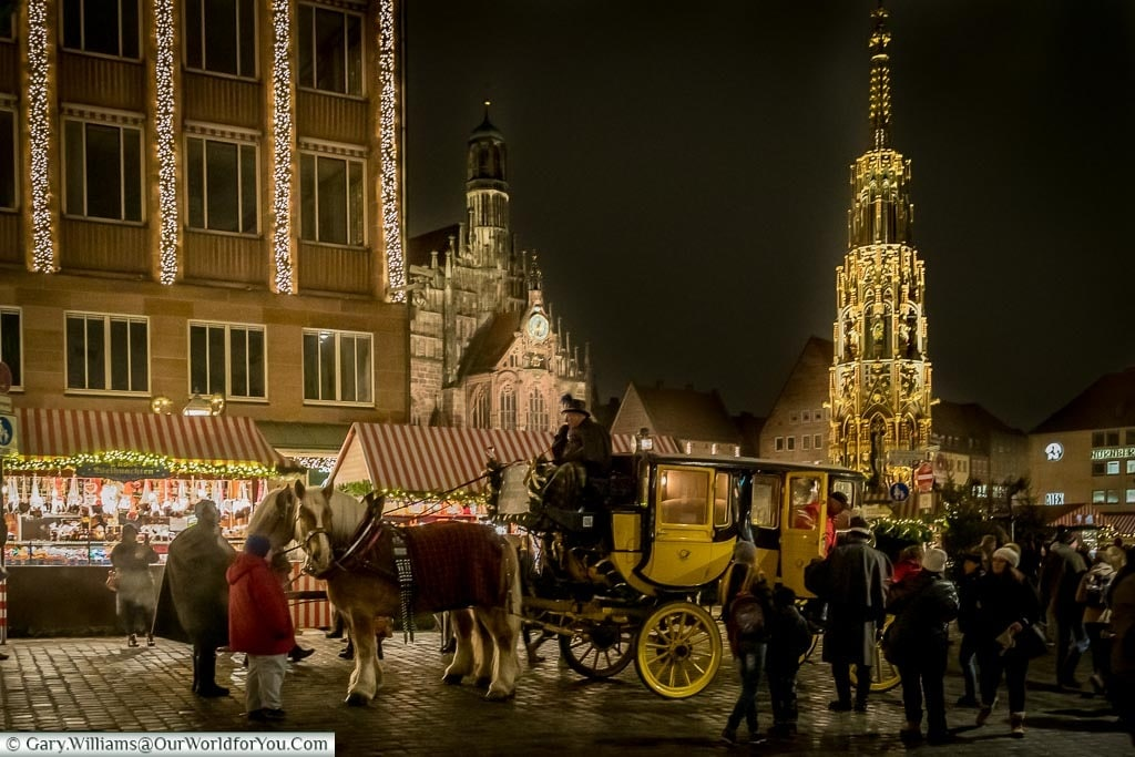 A traditional yellow & black carriage drawn by two horses in front of the Schöner Brunnen, a tall, ornate, lit gothic tower on top a fountain.