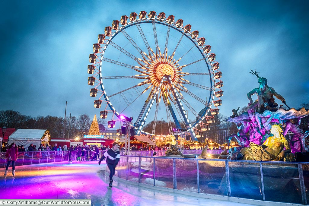 A skater on the ice rink around the Neptune fountain in Berlin, with the giant Ferris wheel in the background.
