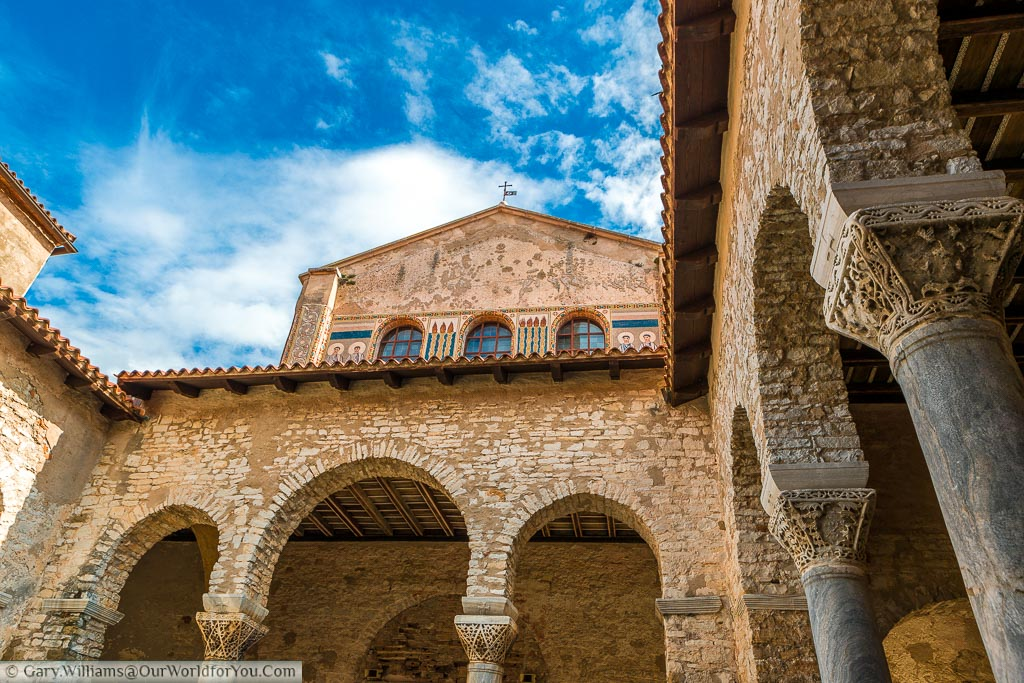 The courtyard of the Euphrasian Basilica with columns topped with ornate capitals and a beautiful blue sky, dappled with the occasional white fluffy clouds.