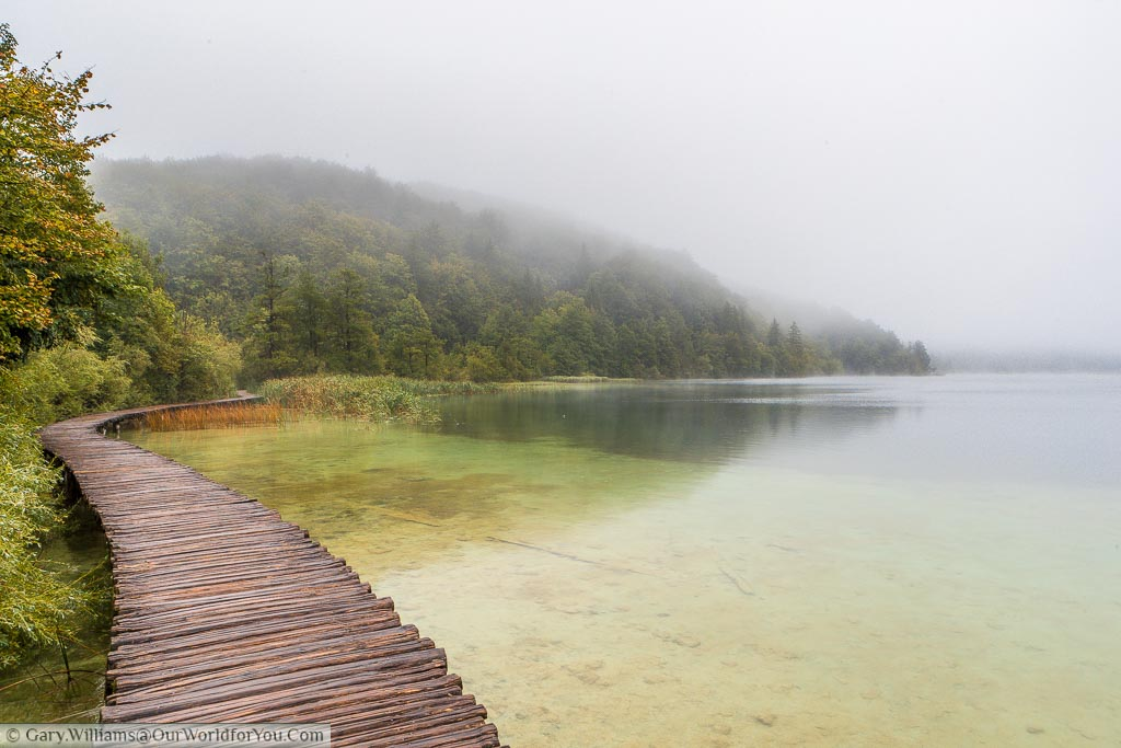 A damp path, constructed of wooden planks, skirts the end of one of Plitvice's many lakes, framed by a tree-covered hill.  A mist hangs over the lake and clings to the hillside.