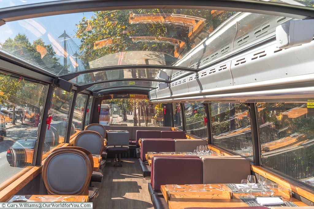 Inside the upper deck of the Bustronome tour bus with its panoramic glass roof.