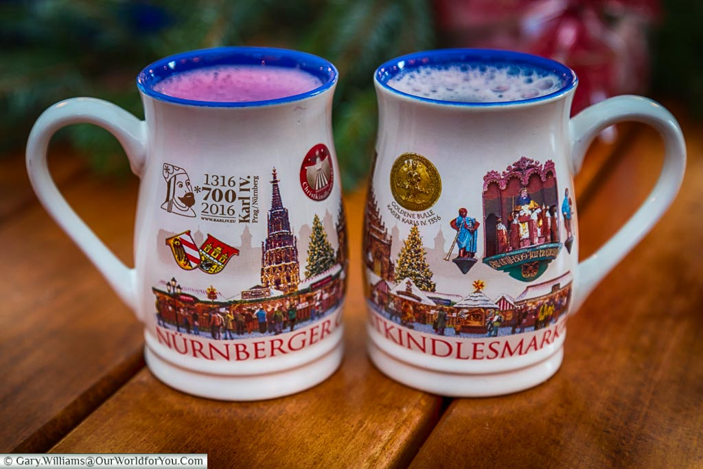 Two mugs of glühwein in the 2016 Nuremberg mugs.  One is the regional version with added blueberries, and the other is a regular red version.