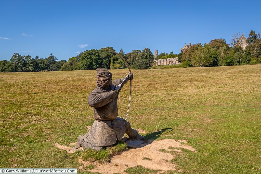A wooden statue of a kneeling archer aiming in the direction of the Abbey from the edge of the battleground.