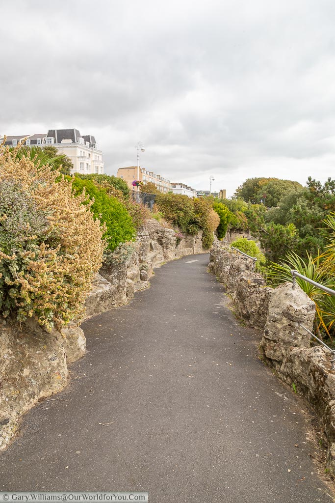 A tarmac path heading down through a man-made rocky landscape that leads towards the beach.