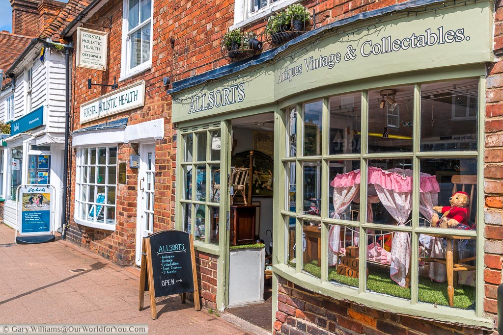 An antiques and collectables shop on the High Street in Headcorn with teddy bear and a small child's bed in the window