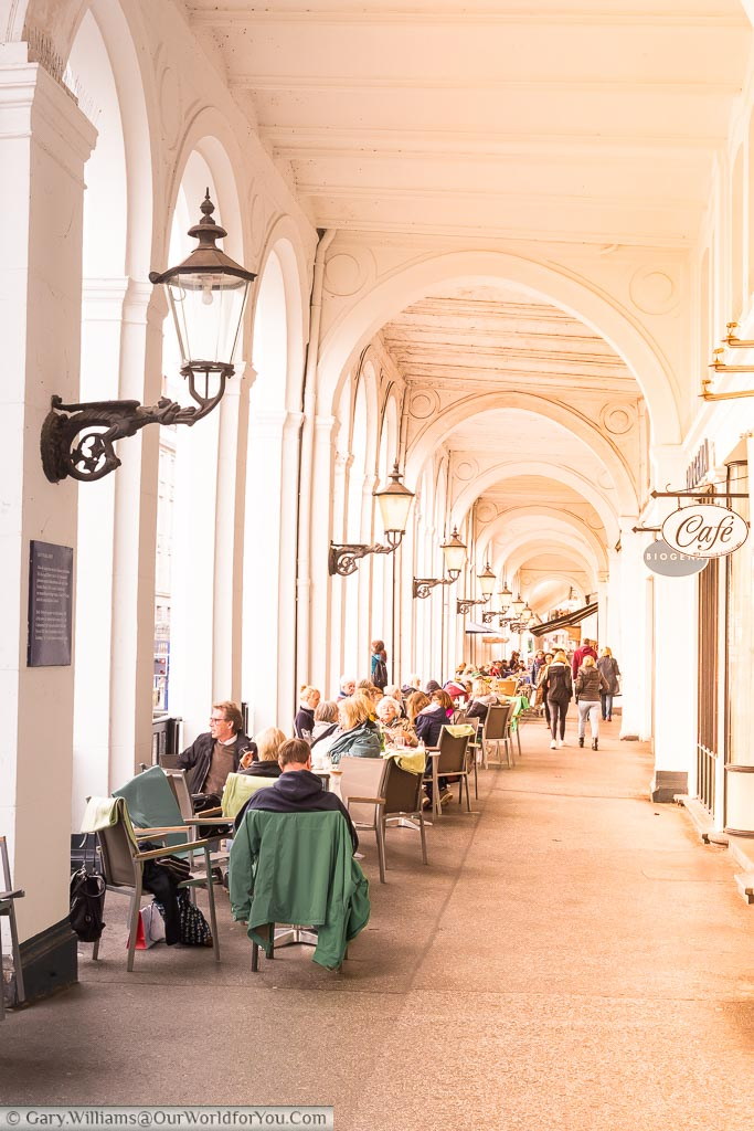 A look along the historic Venetian-style arcade along the waterfront of Hamburg with tables and chairs filled by cafe patrons.