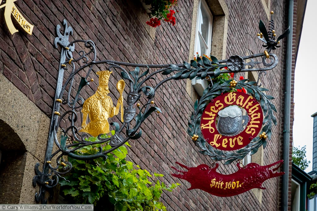 The wrought iron sign of Altes Gasthaus Leve.  The restaurant sign depicts a chef with a wooden sport.